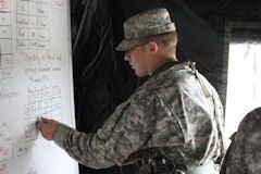 An MSIV cadet updates the status board in a field training exercise (FTX) tactical operations center (TOC).