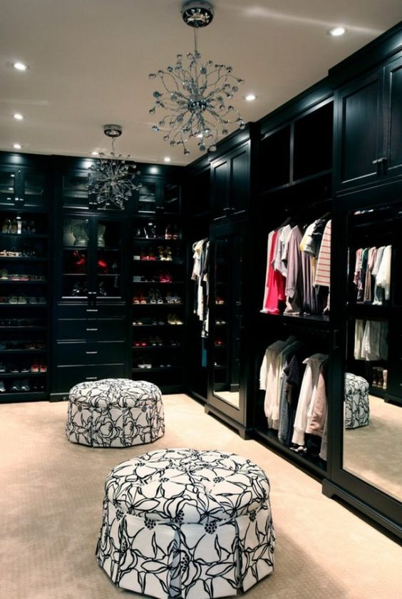 Nicely-built walk-in closet with black cabinets and 2 chairs #dark #closet #storage #organization #allenrothCloset #allenAndRothCloset #closetShelves