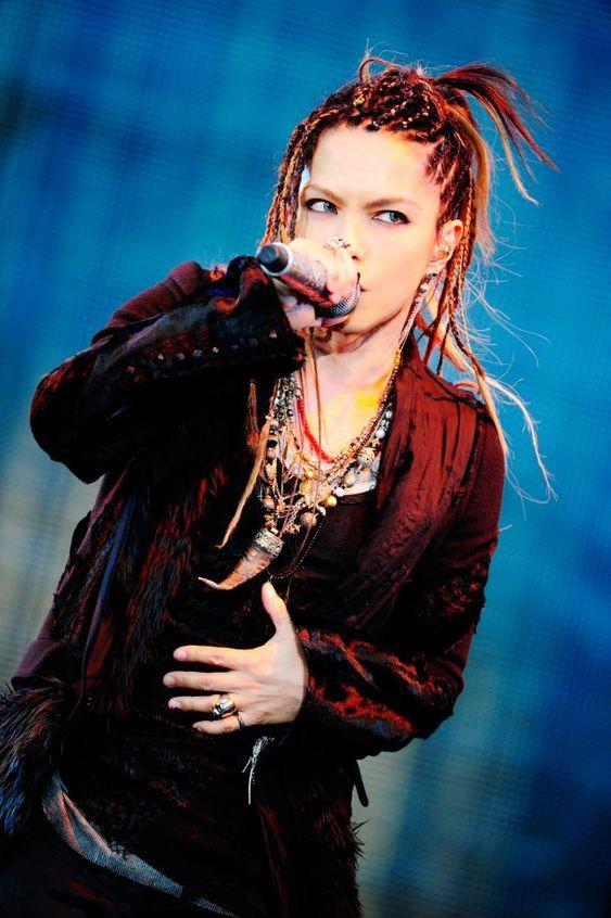 赤いジャケットを着てステージで熱唱しているL'Arc〜en〜Ciel・hydeの画像