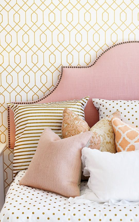 coral, pink and gold girl's room. pattern mix. upholstered headboard with nailhead detail.: