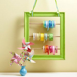organize ribbon- plain wooden frame with bright paint and cafe rods.