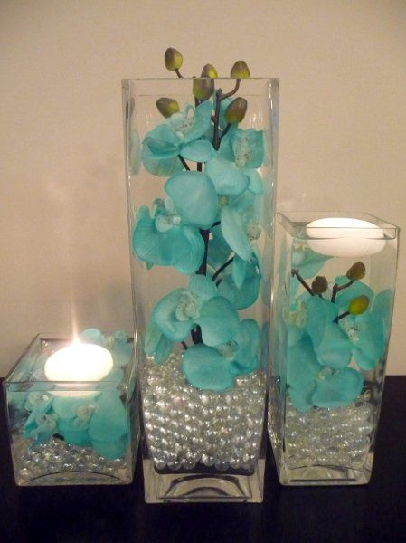 Aqua flower centerpieces use fake orchids place in