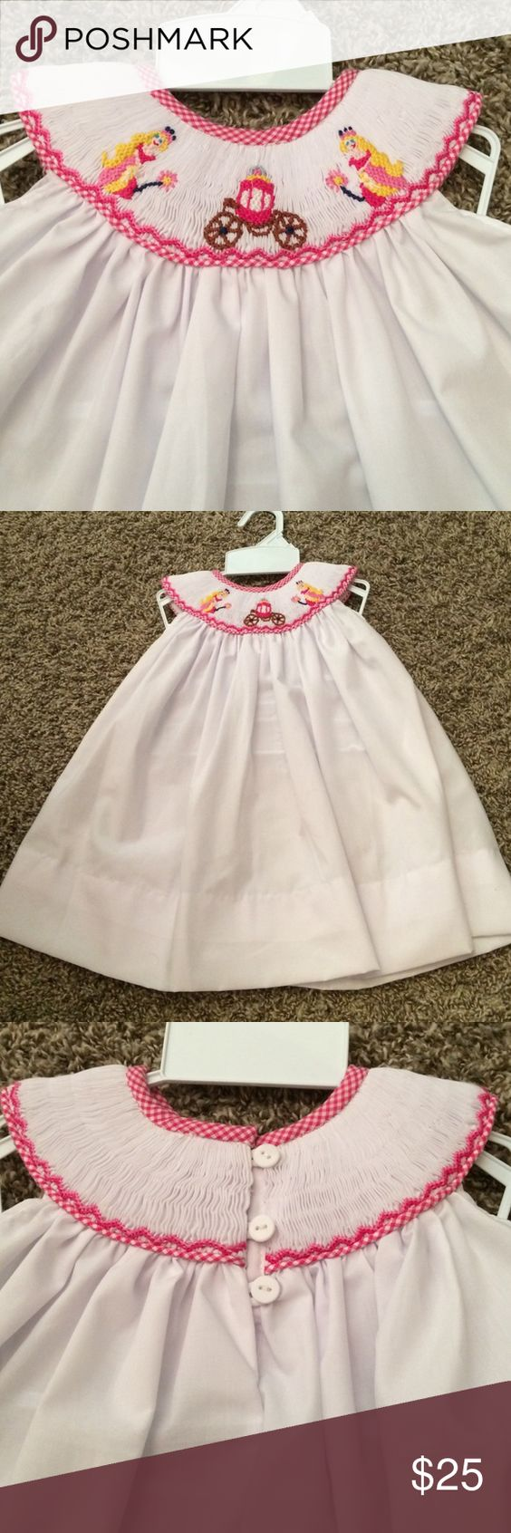 "👑Smocked princess carraige dress White dress, smocked around the neckline with princesses and a carraige and pink gingham around edges. Button up the back. Just THREE left! *12 💕3m-- chest 12.5"" stretched; length from scoop of neck 15.5"". 💕6m-- chest 13"" stretched; length fromscoop of neck 16"". No offers please due to our items already being priced lower than regular store price and Poshmark fees. Select buy now or add to bundle :) NOLA Smocked Dresses Casual"