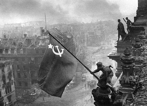 """1945: La hoz y el martillo sobre Berlín. El 2 de mayo un soldado soviético hace ondear la bandera roja de la victoria sobre el Reichstag berlinés; de fondo, las ruinas humeantes de la capital del Reich alemán """"de los mil años"""". La guerra en Europa llega a su final con la derrota militar de Alemania y la liberación del continente tras una larga guerra contra el fascismo en la que murieron millones de personas."""