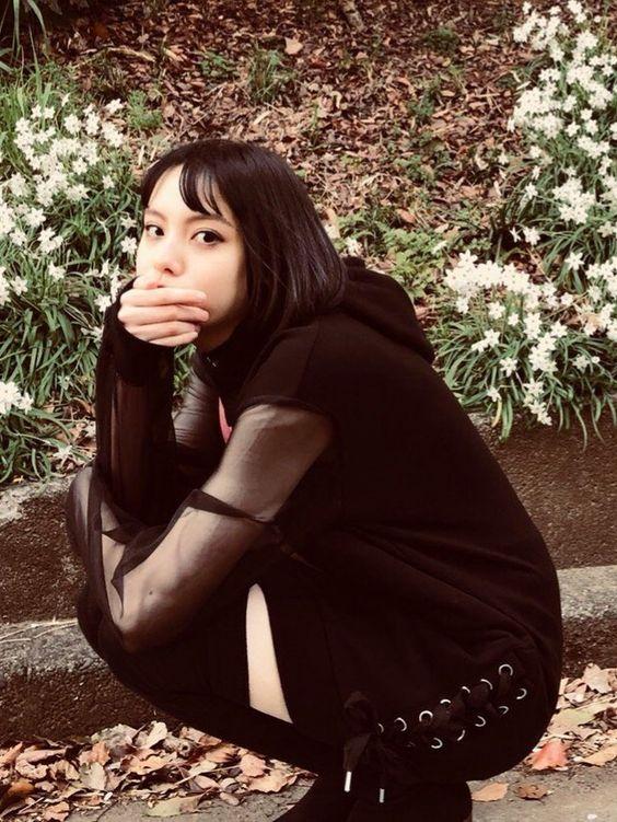 黒い衣装を着てしゃがんでいる渡邊璃生の画像