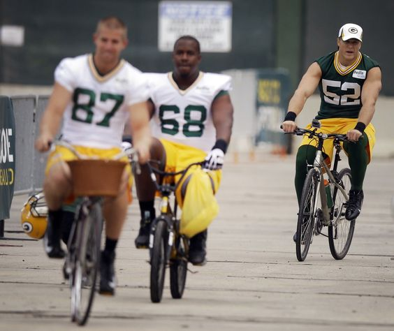 Clay Matthews(52) rides a bike with teammatesJordy Nelson(87) andKevin Hughes(68) toNFLfootball training camp Friday, July 26, 2013