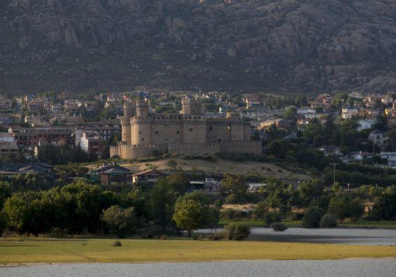 El castillo de los Mendoza, con el embalse de Santillana y La Pedriza de fondo. A la sombra del castillo de los Mendoza, el municipio posee un enclave declarado reserva de la biosfera. Sirvió como plató para el rodaje de diversas películas. En la imagen, el castillo destaca sobre la panorámica de Manzanares el Real.