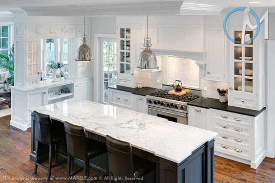 Mix and match here takes on a new meaning when black granite pairs with white cabinets and white granite pairs with black. This is a bright kitchen with just a little bit of muting.