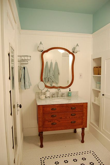 Aqua, vintage white wood paneled walls, black and white floor. Great use of vintage dresser and mirror for vanity