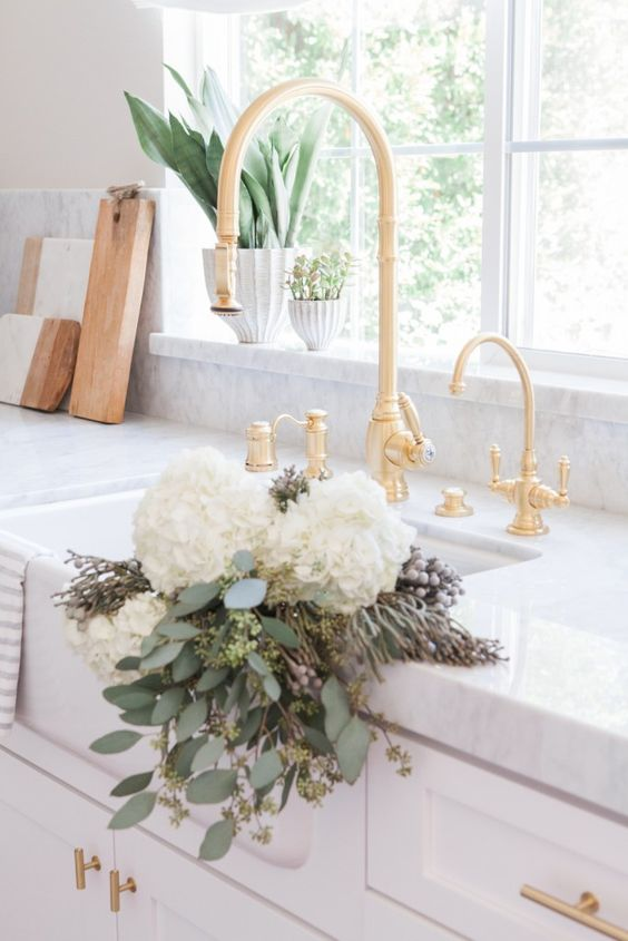 Nicole Davis Interiors White and Gold Kitchen with farm sink, rustic cutting boards, and #brasshardware
