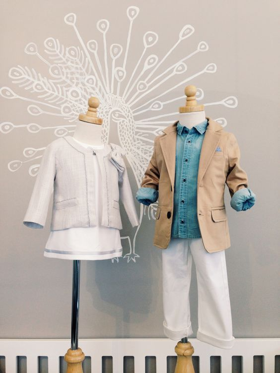 2014 Spring/Summer 2014 Apparel Collection. Left mannequin: Mayoral white dress with silver detail paired with Mayoral tweed jacket with bow and silver detailing. Right mannequin: Mayoral denim button-up paired with Mayoral khaki blazer with blue pocket square detail and Mayoral white chino pant.