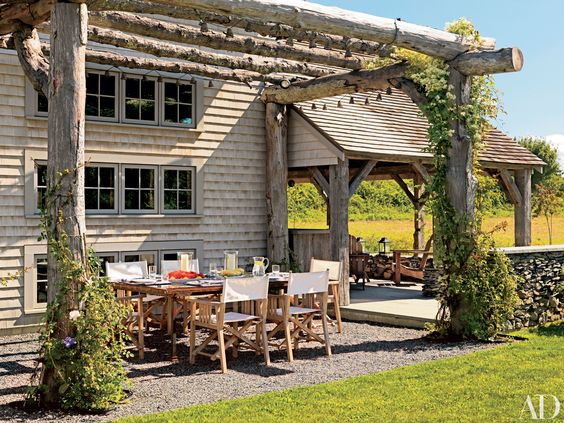 Ellen Denisevich-Grickis renovated her Rhode Island summer home to include a vast wildflower meadow preceding the 3,000-square-foot residence's entrance. A log arbor spans nearly the width of the shingled rear façade, providing shelter for an outdoor dining room.:
