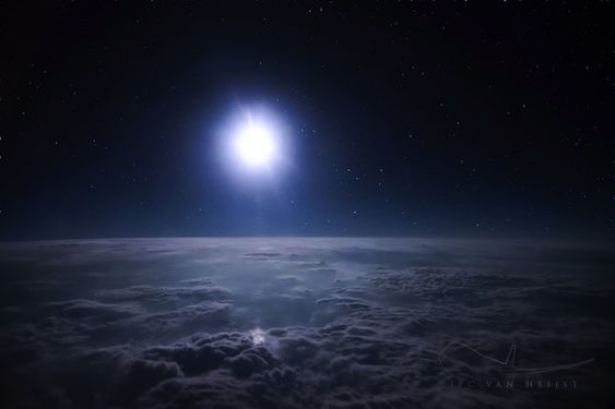 A bright full moon illuminating clouds below.