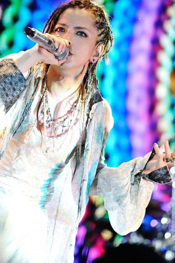 虹色の照明の前で歌っているドレッドヘアのL'Arc〜en〜Ciel・hydeの画像