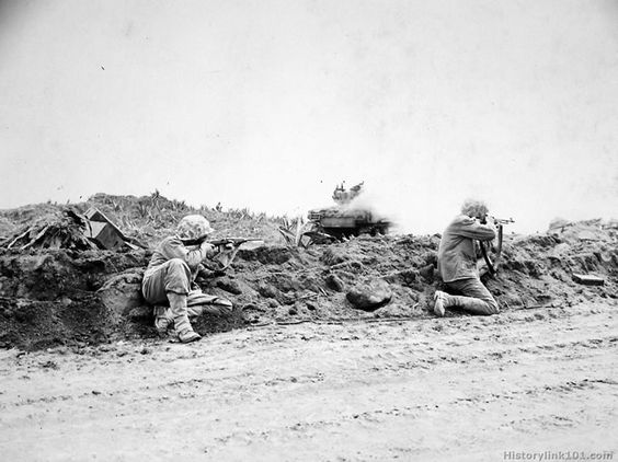 Marine riflemen fire on Japanese positions from behind a burning M ...
