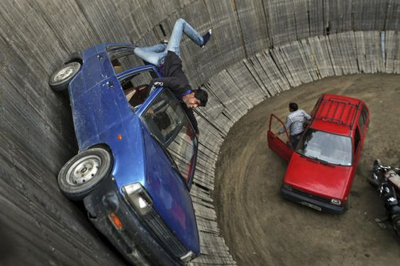 "A stuntman performs in a car at the ""Well of Death"" at an exhibition in Srinagar, India, Friday, May 23, 2014. In the Well of Death, stunt drivers on motorbikes and cars drive in circles"