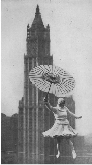 "BIRD MILLMAN, an enormously popular highwire performer of the period, balances mid-air, high above Manhattan; swinging her skirt and waving her parasol, she sails by the gothic spires of the Woolworth Building. This photo appeared in Playboy no 9 July 1924 on page 3. The cover features an illustration of a  TIGHTROPE WALKER and inside ""High Pose for a Playgirl,""  a photo of another tight rope walker - the daring Bird Millman.:"