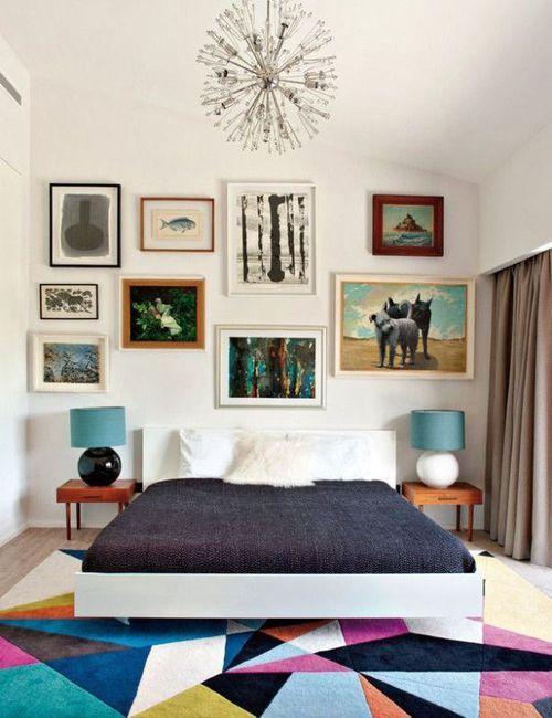 quarto decorado com tapete colorido, cama branca, abajures com cúpula azul, quadros ana parede em cima da cama