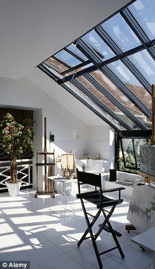 White painted floor and black stool in modern loft conversion living room with large skylight window