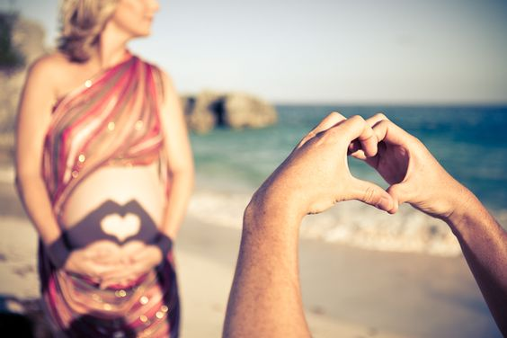 Mother and Father-To-Be casting a heart shadow on the mother's stomach. <3