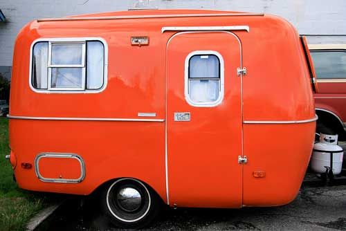 "Isn't she adorable?  Reminds me of a cute couple I met in Moab, Utah.  They had the tiniest orange & navy Boler trailer named ""The Ritz.""  I wonder where Chris & Mokie are now ...    Orange camper:"