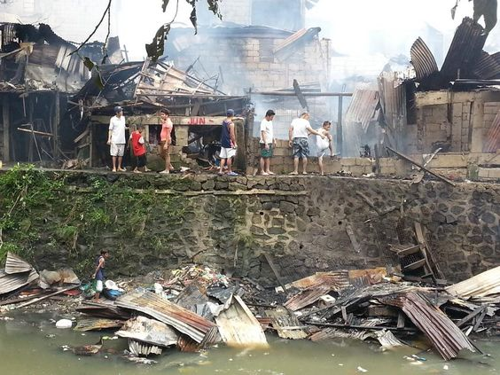 Residents returning to gutted homes in Quezon city after fire destroys thousands. Philippines.  12/31/14