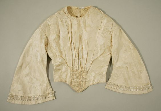 Cream Silk Brocade Evening Ensemble | ca.1845| British| Silk| Length at CB (a): 15.625 in. (39.7 cm) Length at CB (b): 11.25 in. (28.6 cm) Length at CB (c): 41.50 in. (105.4 cm)| Purchase, Irene Lewisohn Trust Gift, 1985| Accession # 1985.140.3a–c | Ensemble includes a second Bodice with Bell sleeves & soft smocked center waist front detail.| 2nd Bodice - Front Detail)