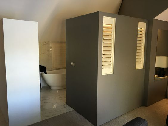 Bathroom privacy (while maintaining openness) using a modesty wall with shutters.