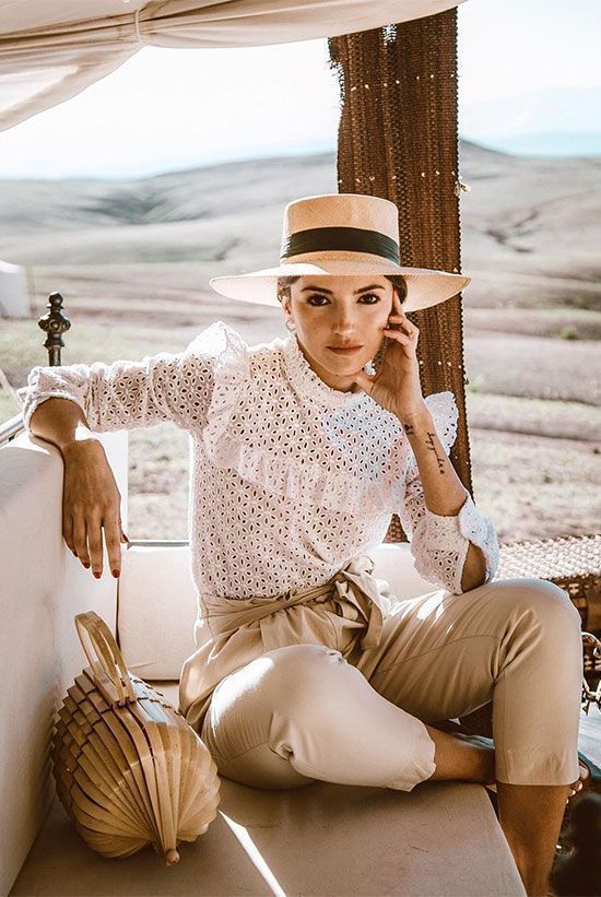 Your Guide To Wearing Neutral Colors This Spring: Fashion blogger 'Lovely Pepa' wearing a straw boater hat, a white lace blouse, beige belted crop pants and a rattan bag.