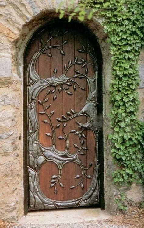 Wood door with metal work depicting a tree scene, set in a stone wall.