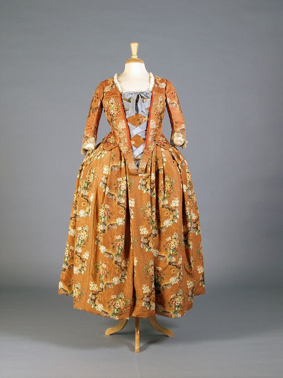 c. 1745 Italian Orange floral bodice and skirt banded together with golden ribbon. Internal burgundy tie strings. Stomacher sides lined with red ribbon tape. (front) Kent State Museum