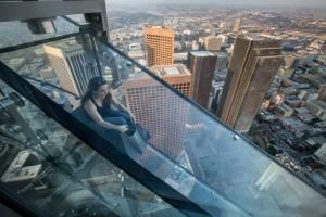 Your guide to visiting Skyspace LA and the Skyslide at the top of the US Bank Tower in Downtown Los Angeles including hours, prices, photos and more.: The Skyslide at OUE Skyspace LA in the US Bank TowerLevel 54 Technology ExhibitIt's Only an IllusionThe Shadow WallSliding Down a SkyscraperThe Sliding Carpet RideSunset SliderThe View from the Sliding CarpetHi-Spy Viewing MachinesThe Sunset ViewA Little RomanceThe Night ViewTop of the TowerSkyspace Photo Station
