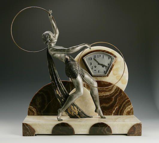 A French Art Deco clock garniture, cast metal and marble, circa 1930. Via Bonhams.com