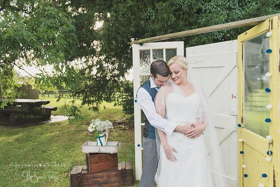 Fishlake Mill, South Yorkshire DIY Wedding. Photography by Folega Photography. Bride & Groom in front of their up-cycled and hand painted wooden doors as a backdrop / home made photo booth. Lovely wooden crates & flowers finish the scene.
