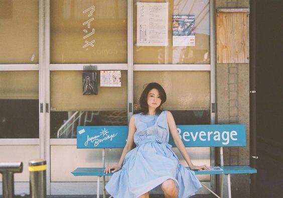 ブルーのワンピースを着てベンチに座っている小林涼子の画像