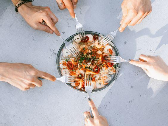 un plato con gambas y calamares rodeado decanos con tenedores, dispuestos a pinchar