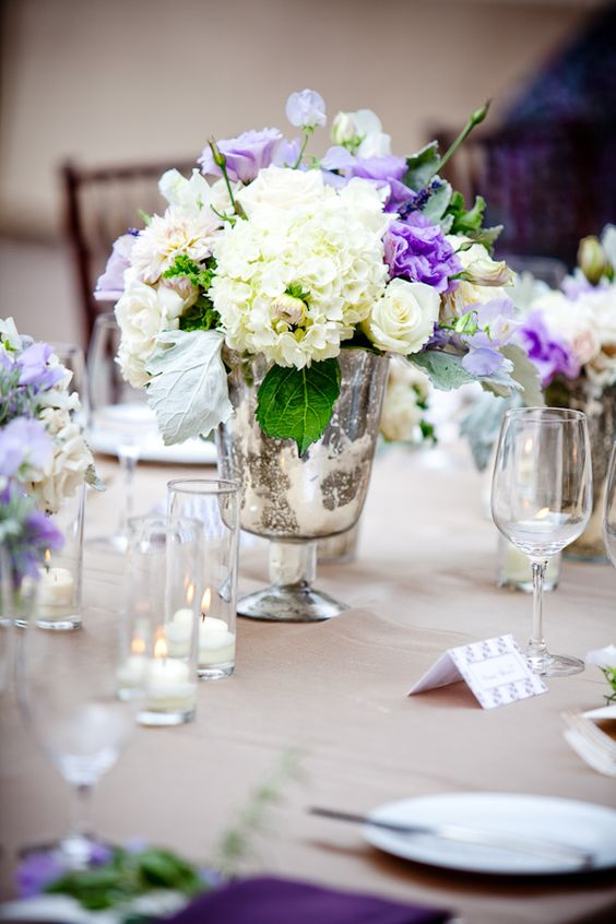 reception floral detail -a beautiful ivory, white, purple, light blue, and green centerpiece in an antique silver vase - photo by New Mexico based wedding photographers Twin Lens
