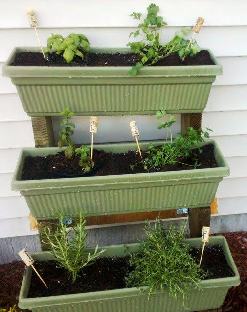 Tiered herb garden made with stair stringers and window box planters and wine cork labels