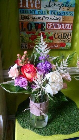 Garden style centerpiece of ivorys,lavenders,coral and peach