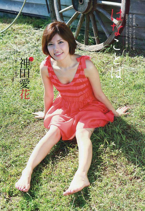 赤いワンピースを着て草むらに座っている神田愛花アナのセクシーな画像