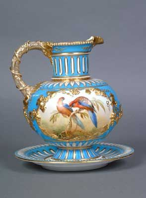 This jug in a turquoise ground and with elaborate gilding is brightly decorated with parrots by John Randall, the famed Coalport bird painter. It dates from c1880.