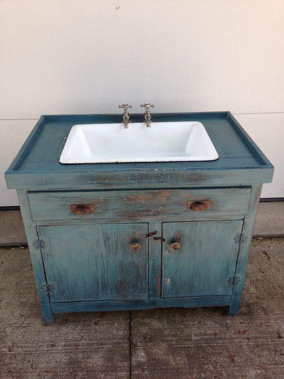 Base cabinet converted to a dry sink with a porcelain sink and faucets added.