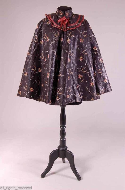 Cape, tot iets over heup, boord en geschulpte kraag katoen sits zwart/bruin; beschilderd bloem + takje veelkleurig; voerin: wol bruin/groen; garnering: lint zijde lichtbruin: