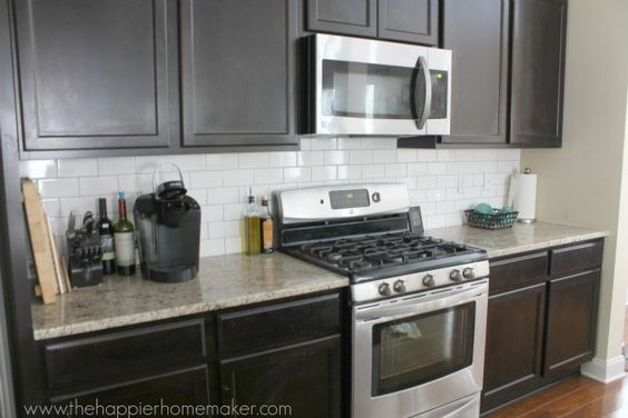 Dark cabinets, white subway tile back splash, medium toned granite