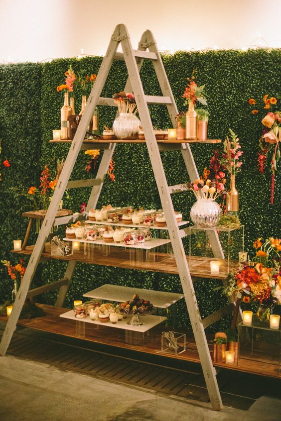 Miniature desserts displayed on a step ladder with faux hedge backdrop - Image by M & J Photography - A chic city wedding in London's West End with a navy, gold & pink colour scheme, stylish decor, Jimmy Choo Shoes & bespoke wedding rings.