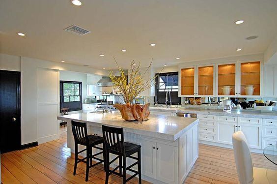 Long gourmet kitchen with a compact island with marble counter top, white upper cabinets with glass fronts and wide plank stained natural wo...