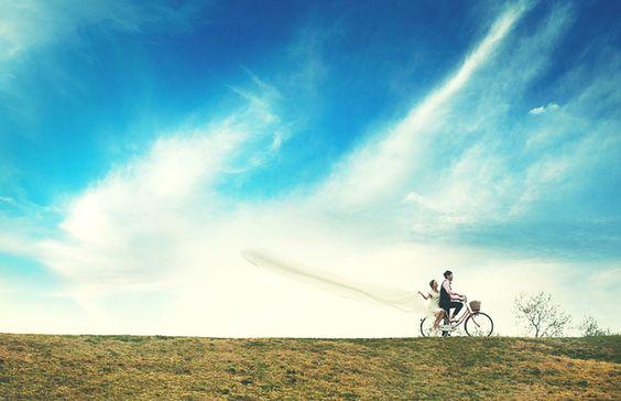河原を仲良くサイクリング。風に舞い、空にたなびくブーケが、これからの2人の幸せを予感させます。