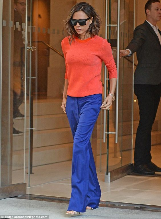 Victoria Beckham wearing a coral sweater & royal blue trousers from her own collections.