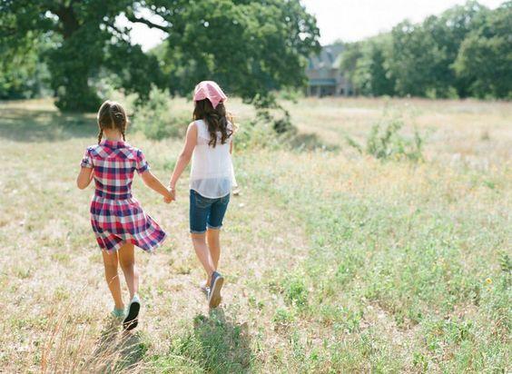l'image du photographe jenny mccann des filles marchant dans les mains de terrain tenant