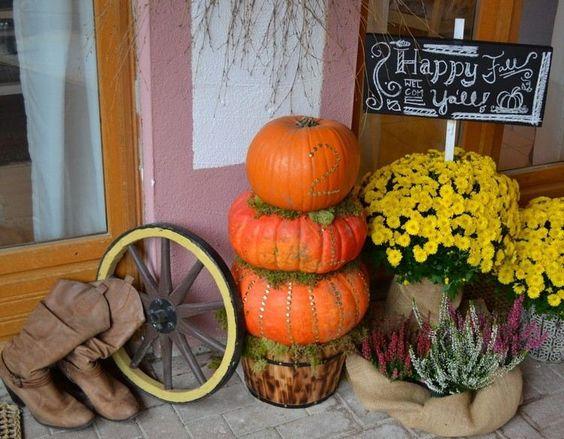 Turm aus Kürbissen und Moos, Holzrad und Blumen